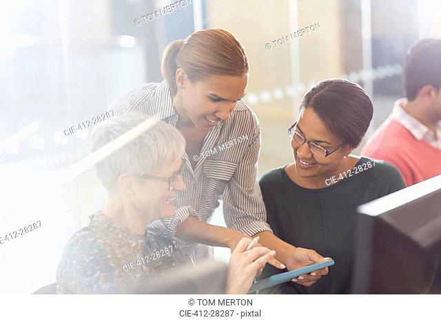 Businesswomen with digital tablet at computers in office