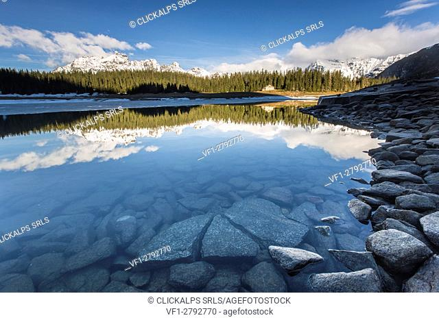 The spring thaw melts ice while snowy peaks are reflected in Lake Palù Sondrio Malenco Valley Valtellina Lombardy Italy Europe