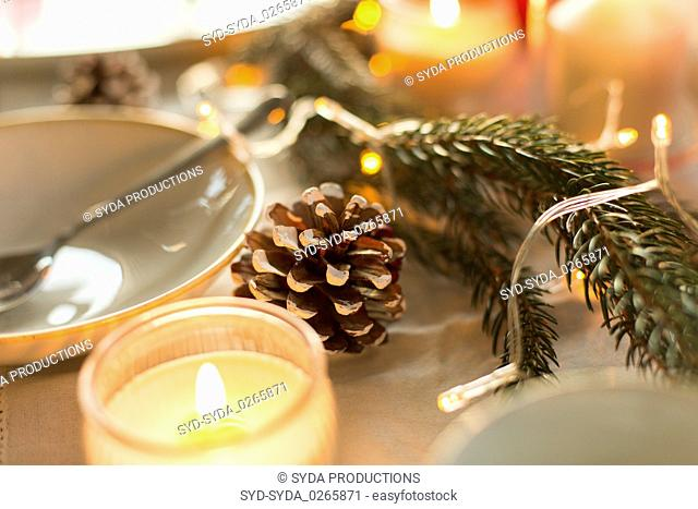 pine cone and candles burning on christmas table