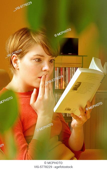 Eine junge Frau liest ein spannendes Buch in ihrer Wohnung, 2005 - Germany, 17/07/2005