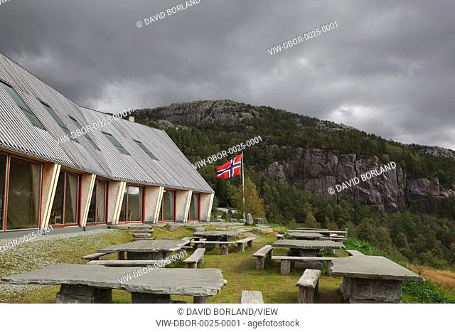 Preikestolen Mountain Lodge, Strand, Norway. Architect Helen & Hard, 2008. South elevation against stormy sky with outdoor seating and Norwegian flag