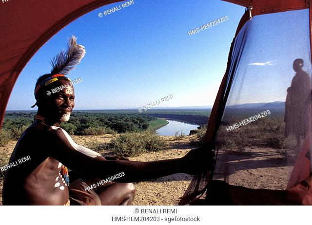 Ethiopia, Lower Omo Valley, listed as World Heritage by UNESCO, a Karo Tribe member opens the tent of a foreign visitor showing one of the most beautiful...