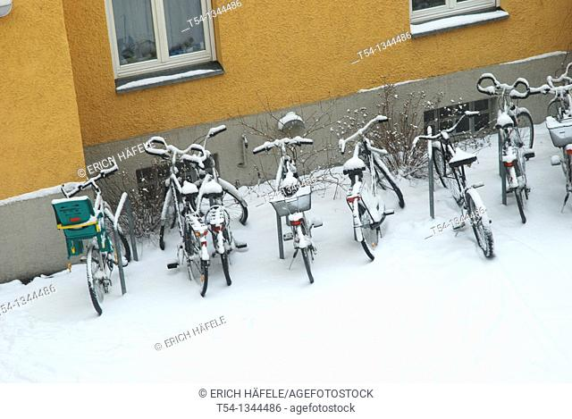 Fresh snow lies on parked bicycles