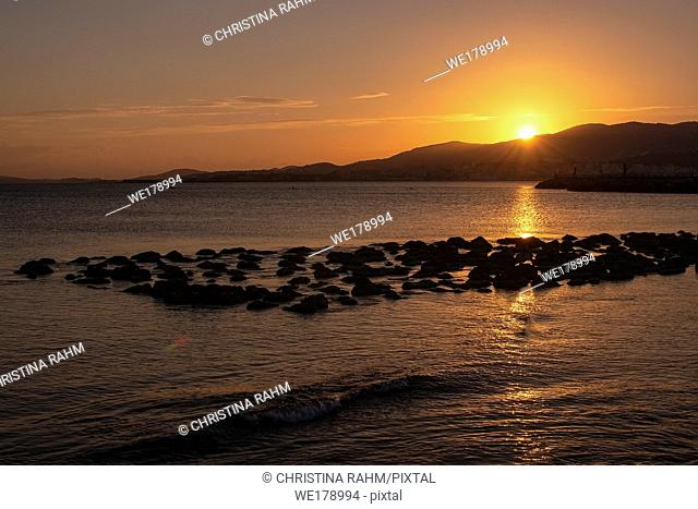 Beautiful golden sunset over mountains and ocean with string of rocks in Majorca, Spain