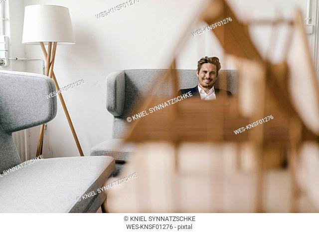 Smiling man on couch with architectural model in foreground