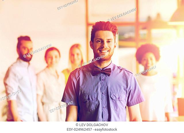 business, startup, people and teamwork concept - happy young man with beard and bow tie over creative team in office