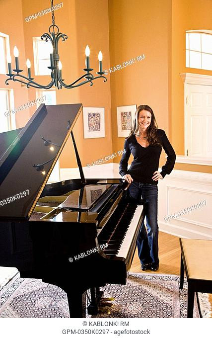 Portrait of smiling young woman standing next to piano