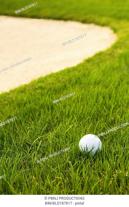 Close up of golf ball near sand trap on golf course