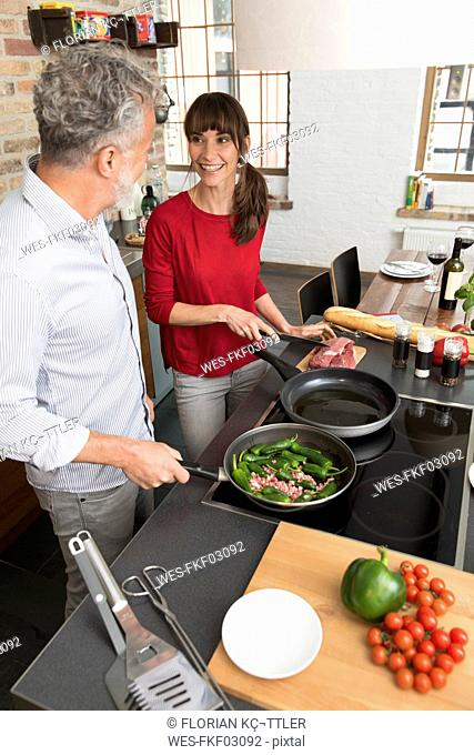 Couple in kitchen, preparing food toghether