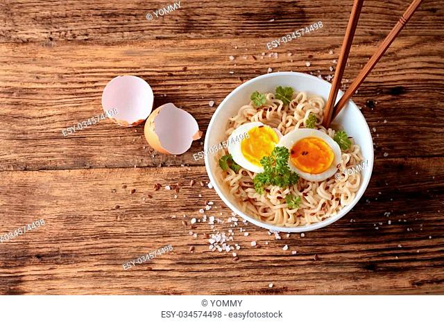 Horizontal photo with top view on old wooden table with white bowl full of chinese soup noodles with parsley and egg slices