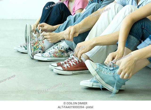 Four teen friends tying laces, all wearing canvas shoes