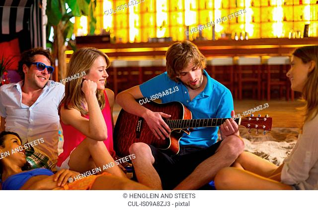 Young man playing guitar to friends in bar