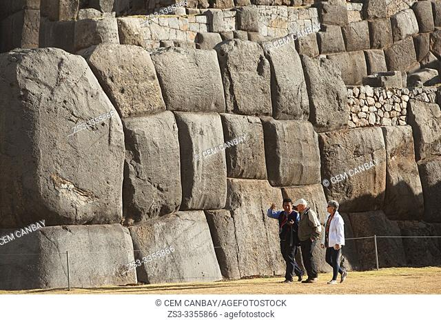 Visitors and a local guide at the The Saqsaywaman archaeological complex, a massive fortress of the Incas, overlooking the Inca navel of Cusco, Peru