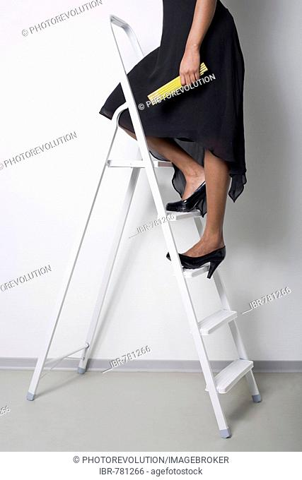 Dark-skinned woman wearing a black dress and high heels standing on a ladder, holding a yardstick