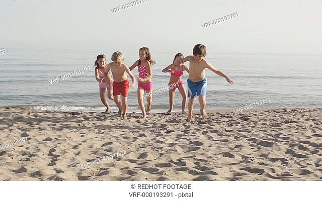 Slow motion of five children running towards camera on beach