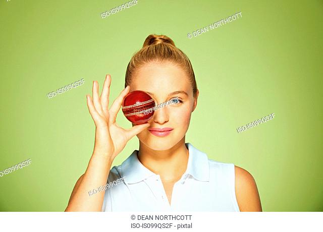 Young woman holding cricket ball over her eye