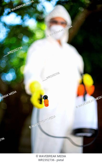 Man wearing protective workwear while spraying insecticide