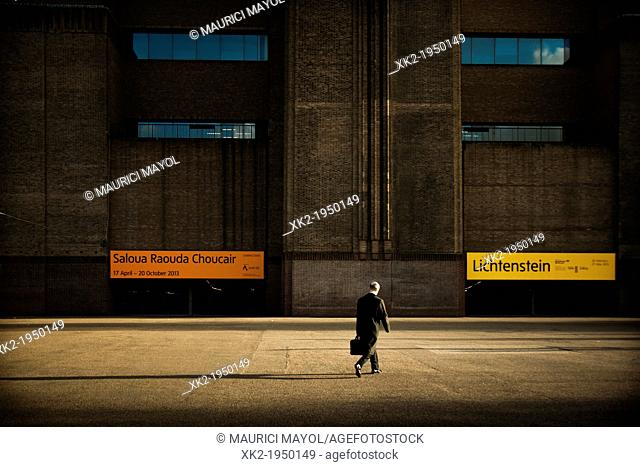 One man walking fast paced in front of the Tate Modern main entrance, London, UK