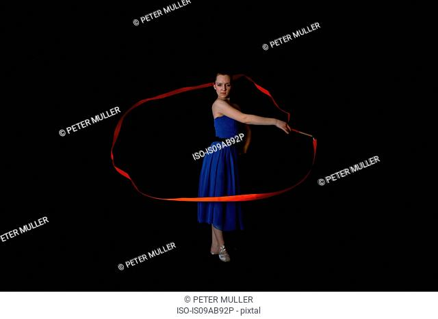 Dancer with ribbon on black background