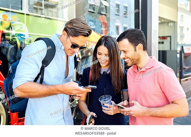 UK, London, Portobello Road, three smiling friends looking at cell phone
