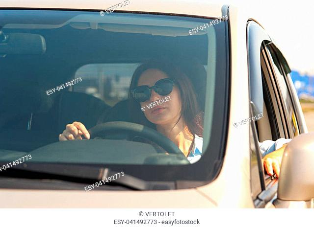 Stylish attractive young woman in sunglasses sits at the wheel of her luxury car and looks at the camera on warm sunny day