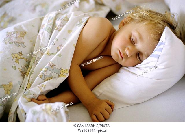 Two year old girl asleep in bed, France
