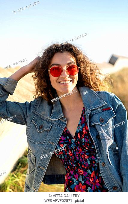 Portrait of happy young woman with curly brown hair wearing red sunglasses leaning on a wall