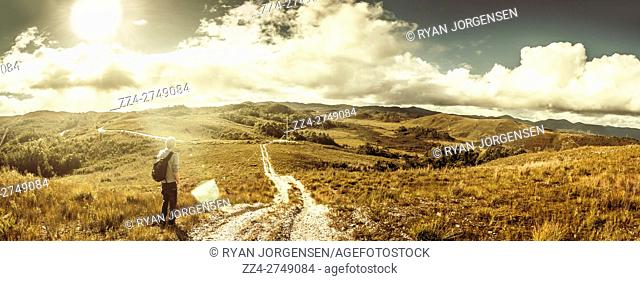 Scenic wide view panorama on a hiking man travelling a dirt road leading though the amazing country of western Tasmania. Taken Zeehan, Australia