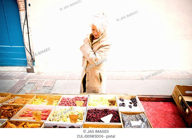 Mature female shopper looking at dried food at local french market