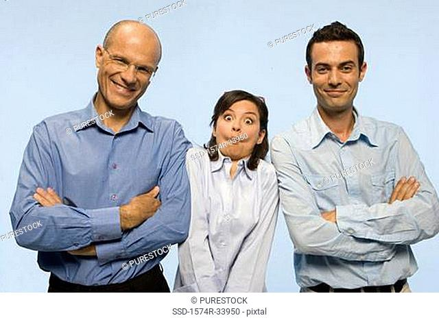 Two businessmen standing with their arms crossed and a businesswoman making a face between them