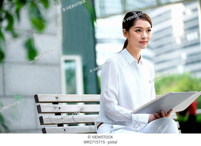 Business young woman sitting on a bench