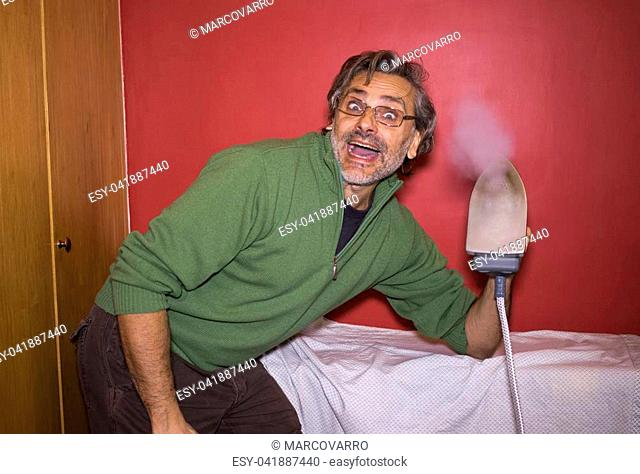 Happy mature man ironing, housework concept
