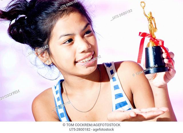 Teenage girl athletics trophy in studio setting