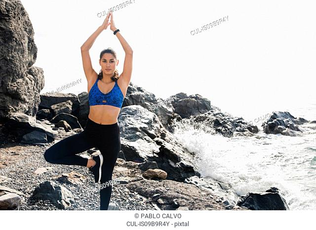 Young woman practicing yoga standing tree pose on beach, Las Palmas, Canary Islands, Spain