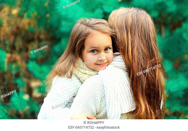 Happy little girl child hugging mother in winter day
