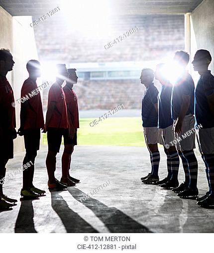 Silhouette of soccer teams greeting in locker room