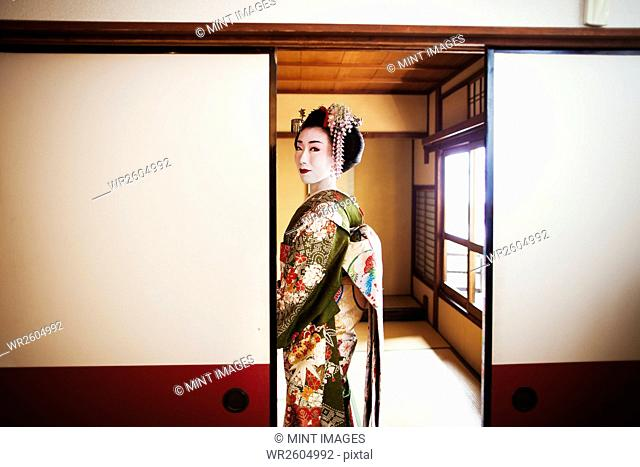 A woman dressed in the traditional geisha style, wearing a kimono and obi, with an elaborate hairstyle and floral hair clips