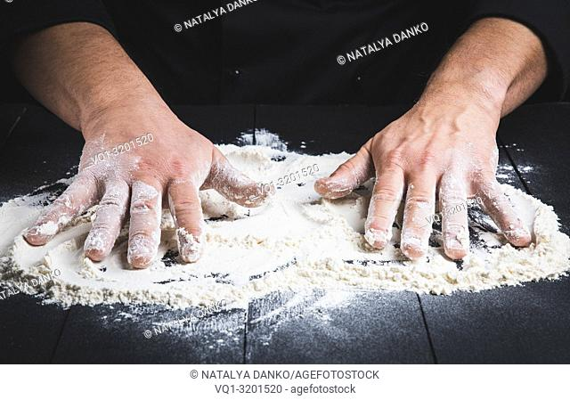 white wheat flour on a black wooden table and two male hands, close up