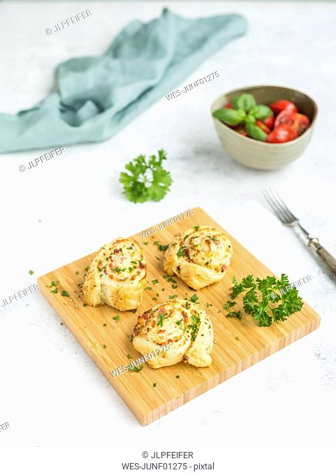 Sticky buns with feta, cream cheese, bacon and parsley on wooden board