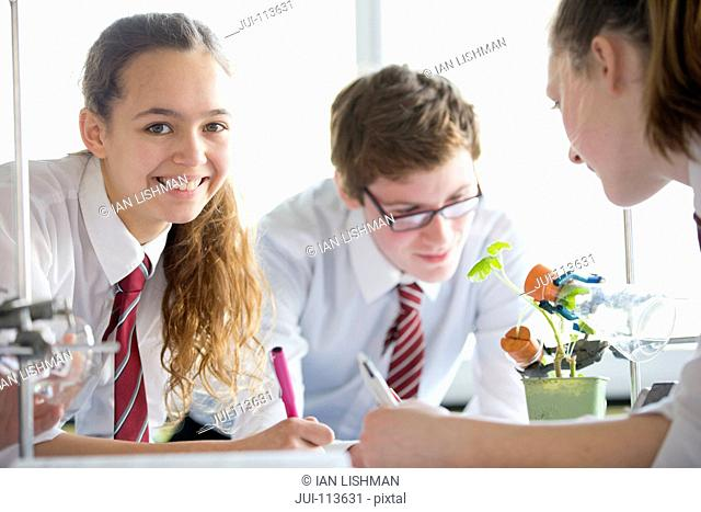 Portrait high school students conducting scientific experiment in biology class