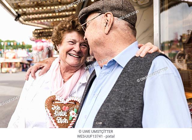 Happy senior couple with gingerbread heart on fair