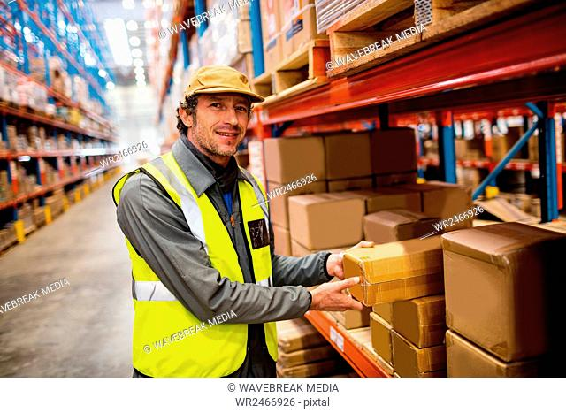 Warehouse worker taking package in the shelf