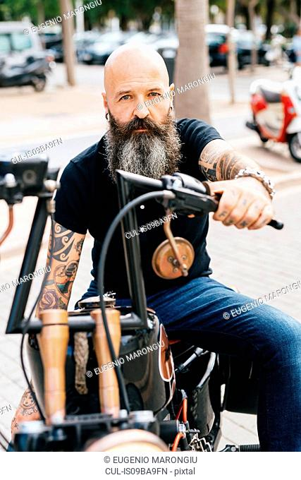 Portrait of mature male hipster astride motorcycle in parking lot