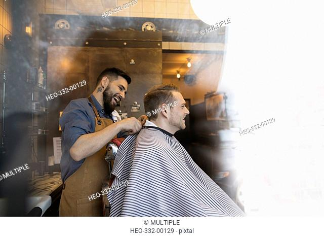 Smiling male barber fastening salon cape on client in barbershop