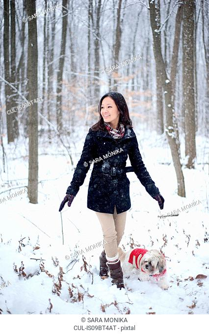 Young woman walking dog in snow covered forest, Ontario, Canada