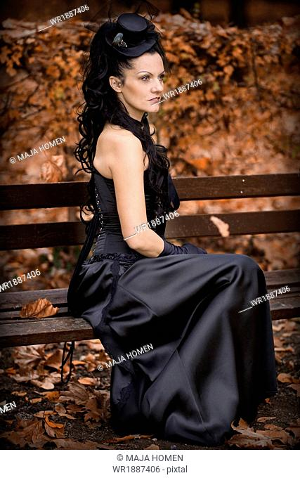 Young woman in Gothic style fashion sitting on a bech in forest, Croatia, Europe