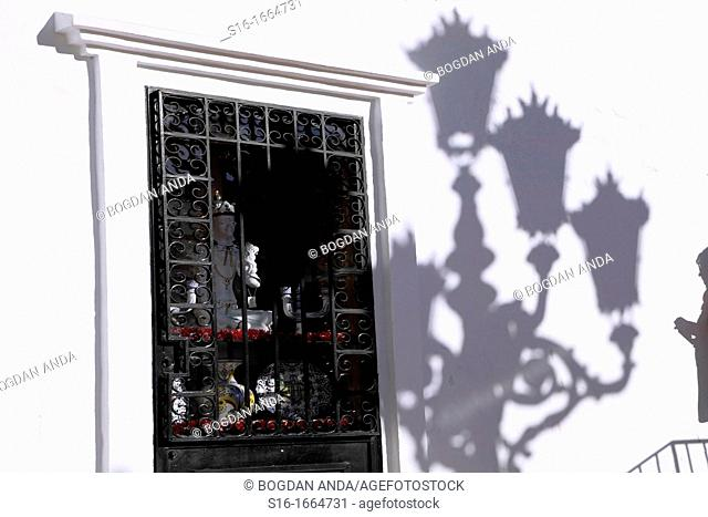 Mijas Pueblo, Spain, Costa del Sol, Malaga province, Andalusia, - Shop window with a display of Buddhist objetcts, accompanied by maching pattern shadows of a...