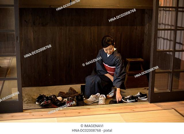 Mid Adult Japanese woman placing shoes properly