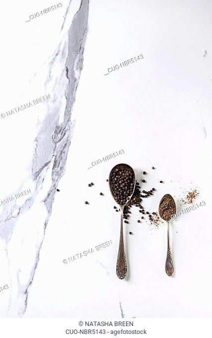 Black pepper peppercorns and ground powder in vintage spoons over white marble texture background. Top view, space