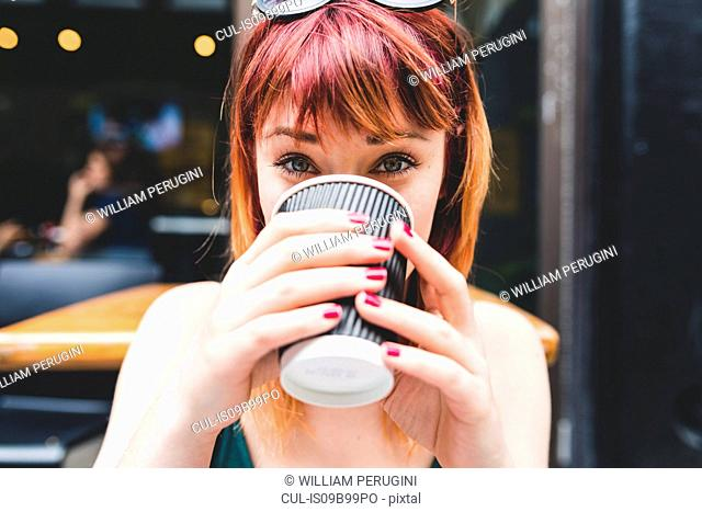 Portrait of young woman drinking coffee at sidewalk cafe table